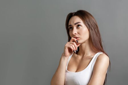 The concept of searching for ideas and information. Portrait of a pensive young Caucasian woman putting her finger to her mouth. Gray background. Copy space.