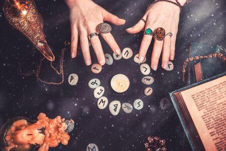 Astrologie und Esoterik. Weibliche Hexenhände beschwören über den Runenkreis. Auf schwarzem Hintergrund liegen Wahrsagerunen, ein Buch, kostbare Amulette, eine Kupferlampe und eine Kerze. Staub und Licht. Standard-Bild
