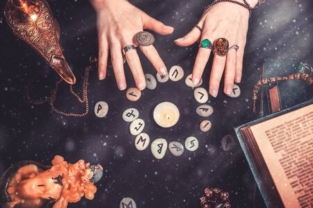 Astrology and esotericism. Female witch hands conjure over the rune circle. On a black background lie fortune-telling runes, a book, precious amulets, a copper lamp and a candle. Dust and light.