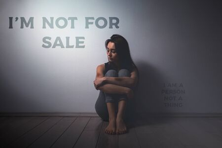 Young sad woman with beatings on the body, sitting disheveled on the floor in the room. There is a light wall in the background.Human trafficking, sexual slavery concept. The inscription I'm not for sale.