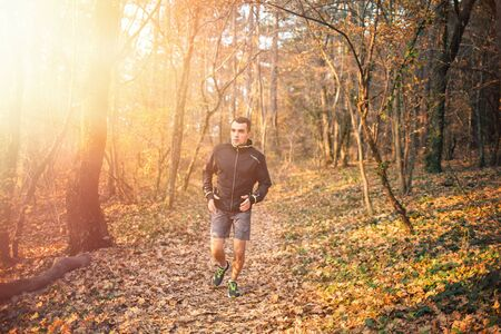 The concept of sport and a healthy lifestyle. A young slender man in sports clothes is engaged in Jogging in the autumn forest or Park. The view from the front. Light and copy space.