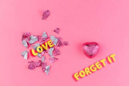 Concept of 14 february or Valentines Day. Chocolate candy-a heart in a pink wrapper, and a torn wrapper in the form of a heart from the candy. Pink background. Copy space. Love and forget it.