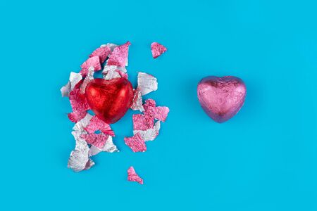 Concept of February 14 or Valentines Day. Chocolate candy-a heart in a red wrapper and a torn wrapper from the candy, and pink bonbon. Light Blue background. Copy space. Banco de Imagens