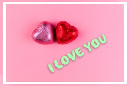 Concept of 14 february or Valentine Day. Chocolate bonbons hearts in a pink and red wrappers. Pink background. The inscriptions I love you and white frame.