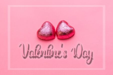 Concept of 14 february or Valentine Day. Chocolate bonbons hearts in a pink wrapper. Pink background. Valntines Day and frame. Banco de Imagens