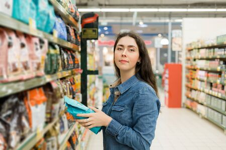 Compras en la tienda de comestibles. Una joven morena sosteniendo un paquete con un producto y sonriendo. Piso de la tienda al fondo. Foto de archivo