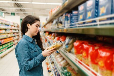 Shopping at the grocery store. A young woman in a denim shirt reads the information on a packet of pasta. In the foreground blurred shelves with products. In profile