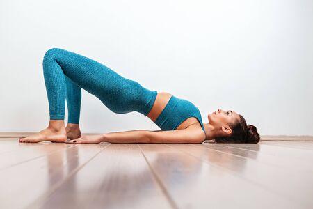 Yoga en sportconcept. Een jonge blanke vrouw is bezig met de warming-up en voert de oefenbrug uit. Witte achtergrond op de achtergrond. Kopiëren