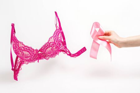 World cancer day. Pink lace bra on a white background and a woman's hand with a pink ribbon. Copy space.