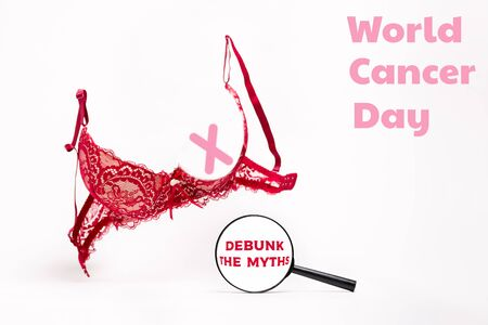 World cancer day. A pink bra on a white background, and a pink ribbon under a magnifying glass. Copy space. Debunk the myths. 스톡 콘텐츠