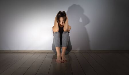 Stress and psychological problems. A young teenage girl is sitting on the floor in a room with her hands clasped behind her head. Light wall in the background. Copy space.