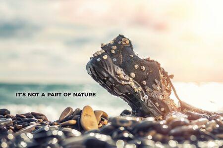 Concetto di protezione ambientale e inquinamento. Una vecchia Scarpa, ricoperta di conchiglie, giace con il naso nelle rocce costiere. L'oceano è sullo sfondo. L'iscrizione Non fa parte della natura. Copia spazio.