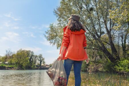 Woman volunteer standing on the river Bank with a bag of garbage. The concept of environmental pollution. Sky, river and trees in the background. Back view. Close up. Banco de Imagens