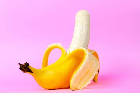An open banana symbolizing the male sexual organ in an erect state. Pink background. Concept of potency and men's health and strength. Copy space. Stock Photo