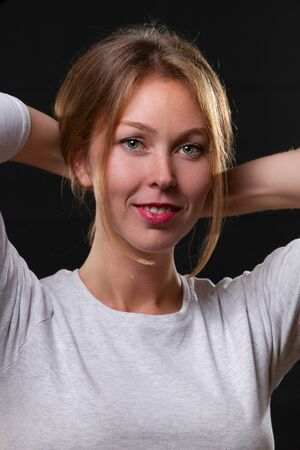 Portrait of a beautiful young blonde woman holding her hair with her hands, on a black background. Stock Photo