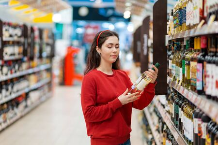 A young Caucasian woman examines a bottle of white wine. In the background, the store shelves are blurred. The concept of buying alcohol in a store. Reklamní fotografie