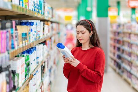 A young Caucasian woman in a red sweater holds a bottle of shampoo and reads the ingredients on the label. In the background, shelves with cosmetics. The concept of buying cosmetics