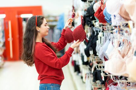 A young Caucasian woman holds a large red bra in a lingerie store and dreams of big bust. The concept of enlargement.