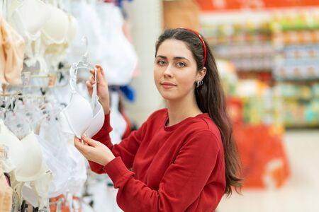 A portrait of young Caucasian brunette woman chooses a white bra in a store. The concept of buying underwear.