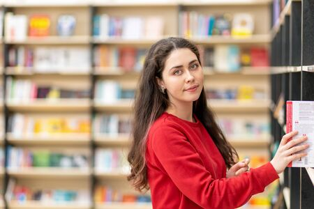 A young Caucasian woman pulls a book from the shelf and smiles sweetly. In the background, shelves of books. Close up. The concept of education and purchase of books.