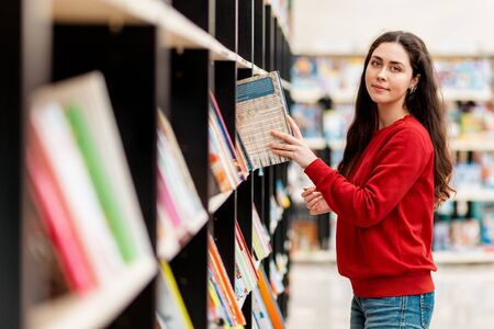 A young Caucasian woman pulls a book from the shelf and smiles sweetly. Blurred shelves of books. The concept of education and purchase of books.