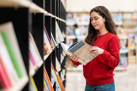 A young Caucasian woman reads a book in her hands, against the background of shelves with books. The concept of education and purchase of books.