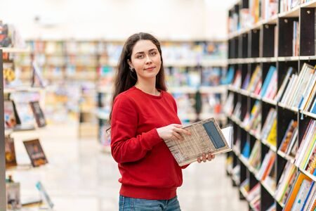 A young beautiful smiling woman poses with a book in her hands, against the background of shelves with books. The concept of education and purchase of books.