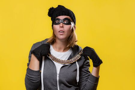 The concept of theft. A blonde woman in a hat, mask and gloves holds jewelry in both hands and tries on. Yellow background and copy space. Stok Fotoğraf