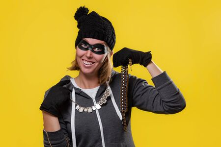 The concept of theft. A blonde in a hat, mask and gloves holds the jewels in both hands and puts them on with a smile. Yellow background and copy space.