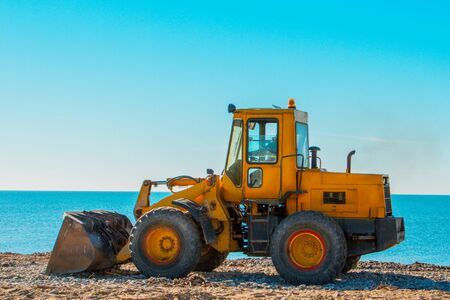 Yellow bulldozer on the background of clear blue sky and seashore. Close up.
