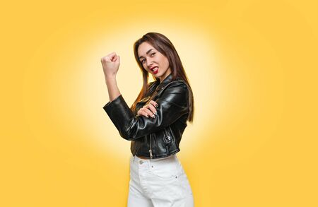 Feminism, girl power, and the concept of equal rights and independence for women. Caucasian young woman in a leather jacket shows biceps. Isolate. Yellow background. Copy.