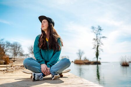 Young Caucasian woman is sitting a hipster on a skateboard with his legs crossed. In the background, the sea and the coastline. Copy space.Concept of sports lifestyle and street cultures. Stock Photo