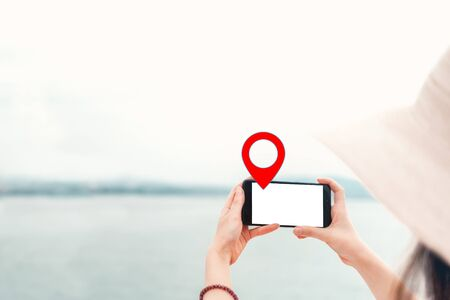 Mock up. The woman in the hat holds the phone horizontally. In the background, the sea and ships. Geolocation icon. Isolate. Foto de archivo