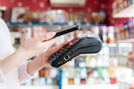 A woman holds a payment terminal and pays for a purchase using a smartphone.On the phone screen-wi-fi network. Shop window in the background. NFC concept, business and banking operations. Standard-Bild