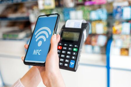 A woman's hands holds a payment terminal with a check and pays for a purchase using a smartphone.On the phone screen-wifi banking operations.