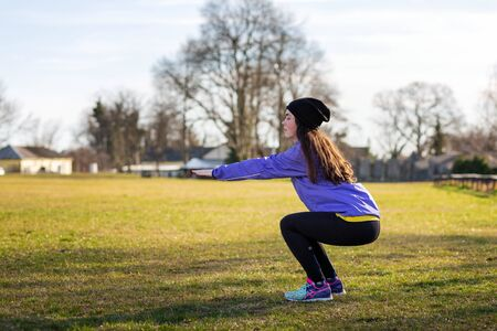 A young Caucasian woman in sports clothes is engaged in warm-up and fitness in the Park, performs squats. The concept of sport, health and active life.