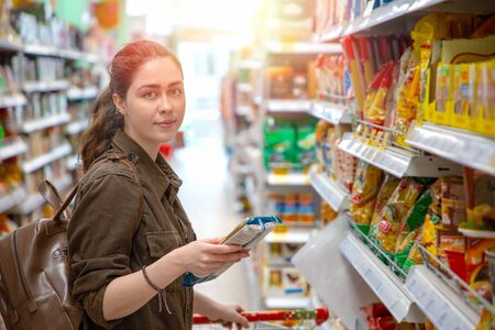 Young pretty woman chooses healthy and quality products in the supermarket. Light.