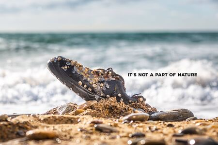 Concept of environmental protection and pollution. An old Shoe, covered with shells, lies in the coastal sand. The ocean ans sky in the background. The inscription This is not part of nature . Фото со стока