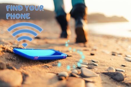The concept of losing your phone. The smartphone lies on the sand, on the beach. In the background, blurred removing footsteps of a man. Inscription Find your phone and a Wi-Fi signal. Foto de archivo