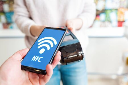 The seller holds a payment terminal, and the man pays for the purchase using a smartphone, online. Top view. On the phone screen network. NFC concept, business and banking operations. Stock Photo