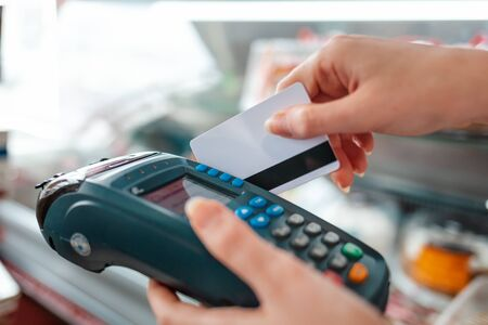 The woman swipes a Bank card through the payment machine to complete the purchase payment. Hands close-up. NFC concept, business and banking operations. Stock Photo