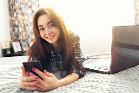 A young brunette woman with a joyful look lies on the bed and uses a smartphone, a laptop is lying next to her. In the background, the interior of the room and the window. Copy space. Sunlight.