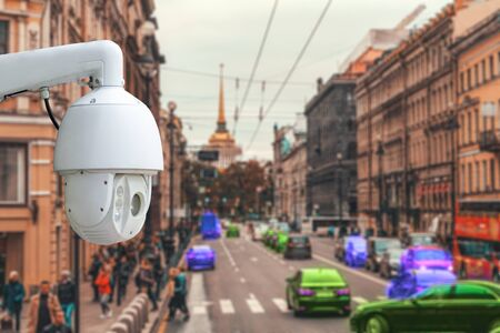 The concept of video surveillance and security technology. CCTV camera on the background of the city road with cars, people and pedestrian crossing 版權商用圖片