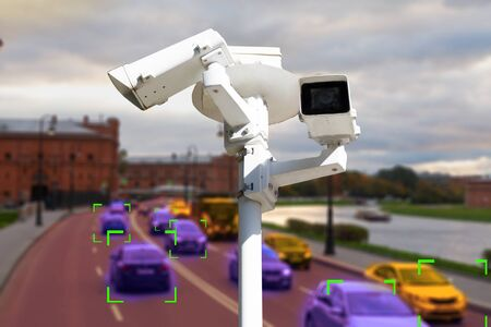The concept of video surveillance and security technology. CCTV camera on the background of a road bridge with traffic in cloudy weather. Definition zone.