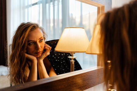 A pretty Caucasian woman looks at her reflection in the mirror with boredom. The concept of self-isolation, psychology and introvertism. Banque d'images