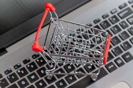 Laptop keyboard with a toy shopping cart standing on it. Close up. Top view. Concept of online shopping and modern technologies.