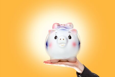Saving money. A man's hand holds a piggy Bank on a yellow background. Copy space. Concept of business, Finance and economy.