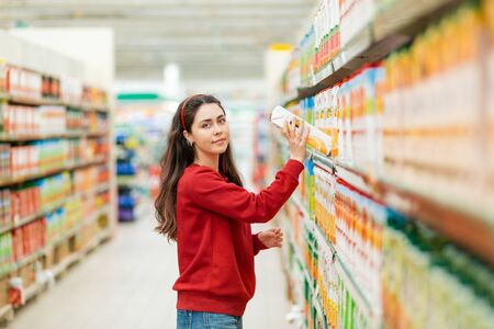 A young Caucasian woman in a red sweatshirt pulls a juice box from the shelf. In the background, rows of store shelves are blurred. The concept of buying products in a supermarket.