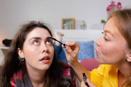 Two young women lie on the bed and make up decorative cosmetics. One woman paints another woman's eyelashes with mascara. Close up. The concept of LGBT relationships and makeup. Zdjęcie Seryjne