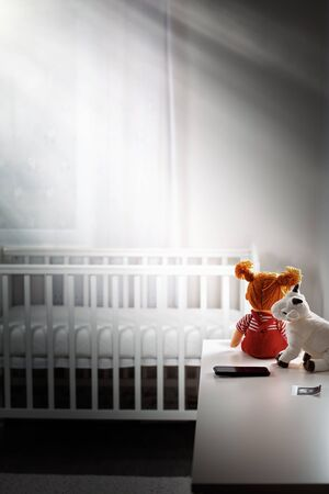 Children's gloomy room with an empty cradle and toys on the dresser. Copy space. Vertical. Concept of abortion and female infertility. Standard-Bild